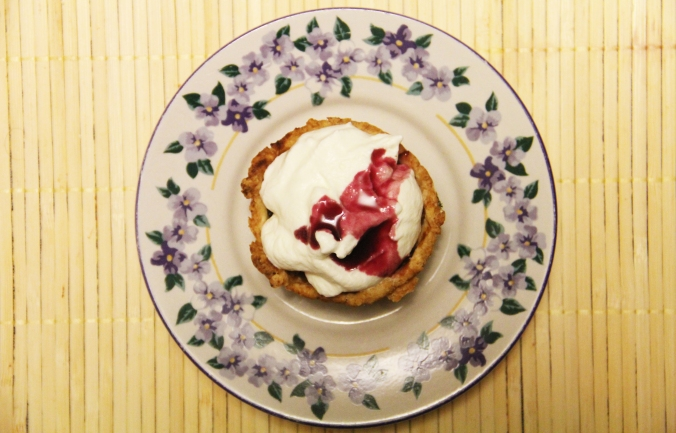 mini apple pie with whipped cream and raspberry syrup